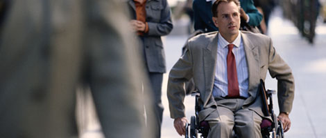 Man in wheelchair moving through a crowd.