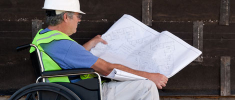 Man in wheelchair looking at blueprints.